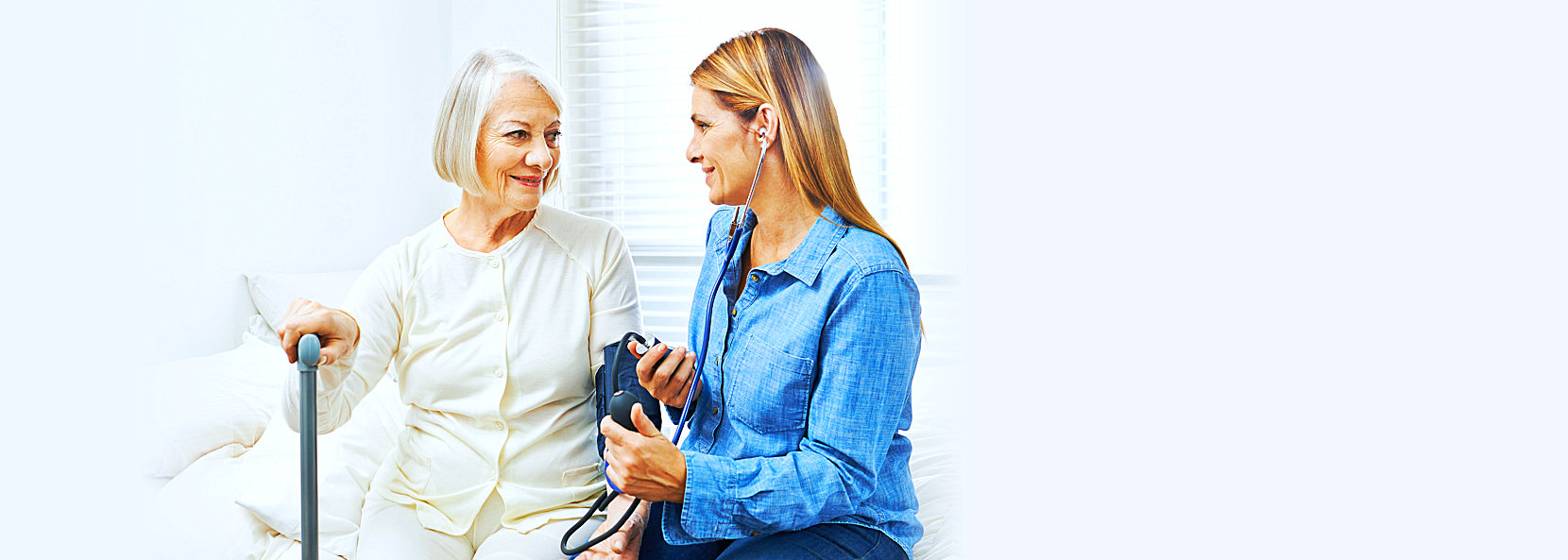 staff check the blood pressure of elder woman